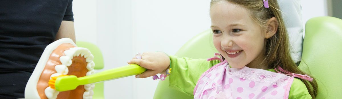 Young girl using teeth brushing model